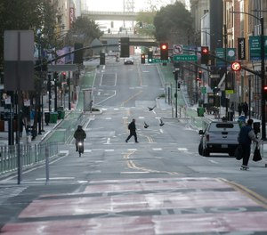 A man crosses a nearly empty street in San Francisco, Tuesday, March 17, 2020. Officials in seven San Francisco Bay Area counties have issued a shelter-in-place mandate affecting about 7 million people, including the city of San Francisco itself. (AP Photo/Jeff Chiu)