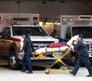 Emergency Medical Technicians wheel a collapsible wheeled stretcher into the emergency room at NewYork-Presbyterian Lower Manhattan Hospital, Wednesday, March 18, 2020, in New York.
