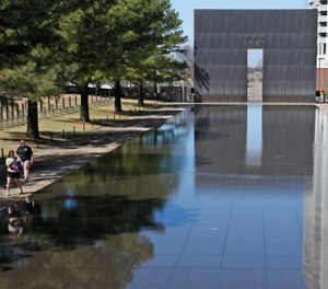 In this March 18, 2020 file photo, visitors walk next to the reflecting pool at the Oklahoma City National Memorial and Museum in Oklahoma City. (AP Photo/Sue Ogrocki, File)
