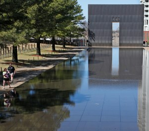 In this March 18, 2020 file photo, visitors walk next to the reflecting pool at the Oklahoma City National Memorial and Museum in Oklahoma City.