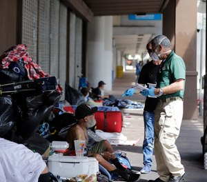 The Miami-Dude County Homeless Trust's chair, Ron Book, left, accompanied the City of Miami Homeless Services Division assistant program administrator Lazaro Trueba, right, talk to a homeless man about washing his hands during the COVID-19 virus outbreak in downtown Miami, on Friday, March 20, 2020.