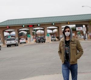 A pedestrian wears a protective mask as he passes the entrance to the McAllen Hidalgo International Bridge, Saturday, March 21, 2020, in Hidalgo, Texas. (AP Photo/Eric Gay)