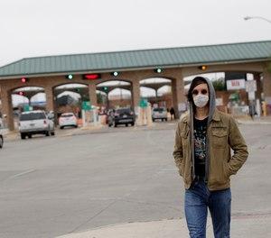A pedestrian wears a protective mask as he passes the entrance to the McAllen Hidalgo International Bridge, Saturday, March 21, 2020, in Hidalgo, Texas.