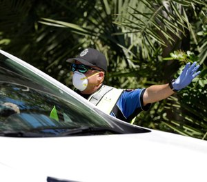 Police check cars and pedestrians at a checkpoint at the entrance to the Village of Key Biscayne, Fla., Monday, March 23, 2020. The village issued an emergency order, banning all travel, starting Monday, within the village by non-residents, with a few exceptions. (AP Photo/Wilfredo Lee)
