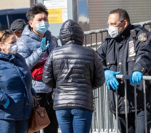 A police officer talks to people who have arrrived to line up outside Elmhurst Hospital Center to be tested for the coronavirus, Tuesday, March 24, 2020, in the Queens borough of New York. (AP Photo/Mary Altaffer)