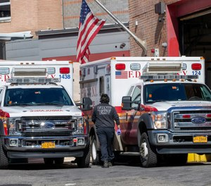 An FDNY EMT works outside Elmhurst Hospital Center, Tuesday, March 24, 2020, in the Queens borough of New York. FDNY union leaders say the department is seeing its highest medical call volume since 9/11 due to the COVID-19 pandemic.