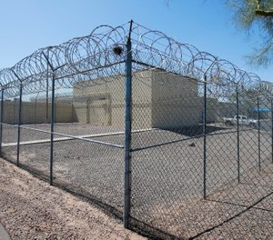 This Saturday, March 21, 2020 file photo shows barbed wire fences at the Maricopa County Estrella Jail in Phoenix. At jails across Arizona, visitation has been suspended, jail workers are checking to see if people being booked are showing symptoms of COVID-19 and inventories have been taken of gloves, masks and other supplies in March 2020. (AP Photo/Ross D. Franklin)
