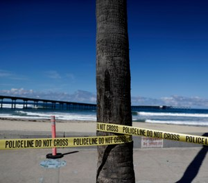 Police tape closes access to a beach Tuesday, March 24, 2020, in San Diego. San Diego tightened restrictions on beach access Monday, as the city reacts to the coronavirus pandemic.