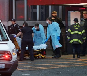 Police, fire and EMS responders respond to a medical call in Seattle, Tuesday, March 24, 2020. The city has booked an entire hotel in the downtown area for first responder quarantine and isolation. (AP Photo/Ted S. Warren)