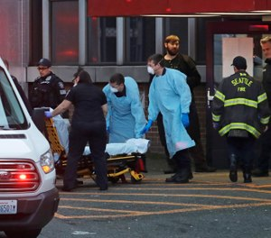 Police, fire, and EMS responders, some wearing masks, gowns, and gloves to protect against the transmission of the new coronavirus, respond to a medical call in Seattle Tuesday, March 24, 2020.