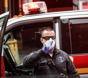 An FDNY medical worker wears personal protective equipment outside a COVID-19 testing site at Elmhurst Hospital Center, Wednesday, March 25, 2020, in New York. (AP Photo/John Minchillo)
