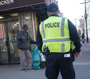 A police officer asks a man to keep moving in an effort to encourage social distancing at an intersection in Newark, N.J., Thursday, March 26, 2020. Police departments are taking a lead role in enforcing social distancing guidelines that health officials say are critical to containing COVID-19. (AP Photo/Seth Wenig)