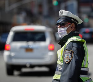 An NYPD traffic officer wearing personal protective equipment stands at a barricade after the city closed down a section of Bushwick Avenue due to COVID-19 concerns, Friday, March 27, 2020, in the Brooklyn borough of New York. (AP Photo/John Minchillo)