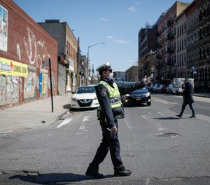 As an increasing number of police officers and deputies have been exposed or tested positive for the coronavirus, workforce reductions will challenge COVID-19 response. (AP Photo/John Minchillo)