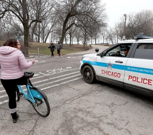 In this March 26, 2020, file photo, a Chicago police officer notifies a cyclist that the trails in Promontory Park, along Lake Michigan, are closed in an effort to limit the spread of COVID-19 infections. (AP Photo/Charles Rex Arbogast, File)