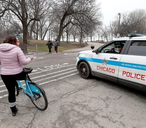 In this March 26, 2020, file photo, a Chicago police officer notifies a cyclist that the trails in Promontory Park, along Lake Michigan, are closed in an effort to limit the spread of COVID-19 infections.