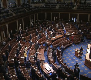 In this image from video, members of the House stand after they passed the coronavirus stimulus package on the floor of the House of Representatives at the U.S. Capitol in Washington, Friday, March 27, 2020. A House representative has proposed a three-month tax holiday for first responders during the COVID-19 pandemic.