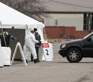 Healthcare officials watch as a vehicle approaches a testing site at the Michigan State Fairgrounds, Friday, March 27, 2020, in Detroit. Detroit and Wayne County officials are considering hazard pay for first responders and other front-line workers during the COVID-19 pandemic. (AP Photo/Carlos Osorio)