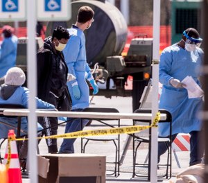Medical personnel wearing protective equipment screen people referred by doctors for COVID-19 testing in a parking lot of FedEx Field, Monday, March 30, 2020, in Landover, Md. (AP Photo/Andrew Harnik)