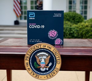 A rapid test kit for COVID-19 developed by Abbott Laboratories sits on a table ahead of a briefing by President Donald Trump about the coronavirus in the Rose Garden of the White House, Monday, March 30, 2020, in Washington. Detroit has entered into an agreement with Abbott Laboratories to order five testing machines and 5,000 test kits and plans to prioritize testing of first responders and healthcare workers.