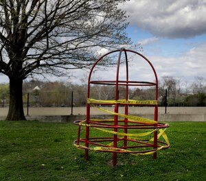 Playground equipment is wrapped in crime scene tape to prevent its use as part of the effort to slow the spread of the coronavirus Tuesday, March 31, 2020, in St. Louis.