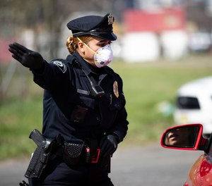 Camden County Police Officer Rodriguez wears a protective mask as she directs people to a COVID-19 testing facility in Camden, N.J., Wednesday, April 1, 2020.