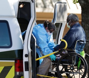 A resident at the Southeast Nursing and Rehabilitation Center is loaded into an ambulance in San Antonio, Wednesday, April 1, 2020. (AP Photo/Eric Gay)