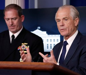White House trade adviser Peter Navarro, who is now serving as national defense production act policy coordinator, speaks about COVID-19 in the James Brady Press Briefing Room of the White House, Thursday, April 2, 2020, in Washington, as Navy Rear Adm. John Polowczyk, supply chain task force lead at FEMA, listens. The Department of Defense announced its first use of the Defense Production Act to boost N95 production on Saturday, April 11.