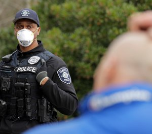 Seattle Police officer Rosell Ellis, left, wears an N95 mask and stands at a distance as he listens to a man officers made contact with during a routine call Thursday, April 2, 2020, in Seattle. (AP Photo/Ted S. Warren)