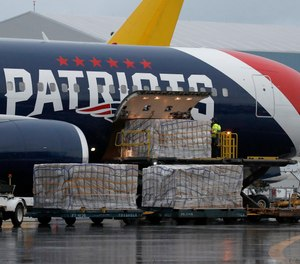 Palettes of N95 respirator masks are off-loaded from the New England Patriots football team's customized Boeing 767 jet on the tarmac, Thursday, April 2, 2020, at Logan Airport in Boston, after returning from China. The Kraft family deployed the Patriots team plane to China to fetch more than one million masks for use by front-line workers to prevent the spread of the coronavirus.