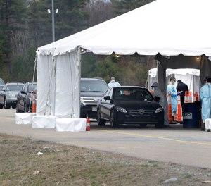 Drivers line up for a coronavirus test at a site in a parking lot at Gillette Stadium, Sunday, April 5, 2020, in Foxborough, Mass. The site, which opened Sunday, is designated specifically for first responders who may have been exposed or are showing virus symptoms. (AP Photo/Steven Senne)
