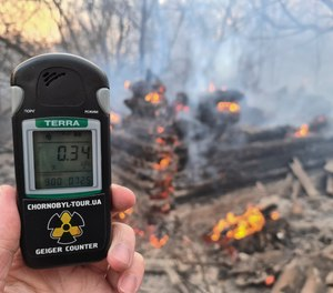 A Geiger counter shows increased radiation level against the background of the forest fire burning near the village of Volodymyrivka in the exclusion zone around the Chernobyl nuclear power plant, Ukraine, Sunday, April 5, 2020.