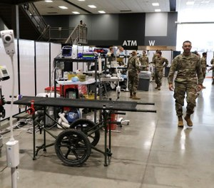Soldiers walk through a treatment area at the site of a military field hospital, Sunday, April 5, 2020, in Seattle. The facility, which will be used for people with medical issues that are not related to the coronavirus outbreak, has more than 200 beds. (AP Photo/Ted S. Warren)