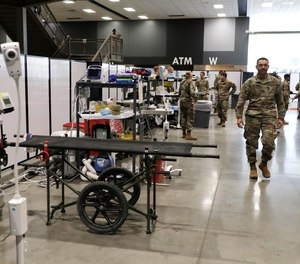 Soldiers walk through a treatment area at the site of a military field hospital, Sunday, April 5, 2020,in Seattle. The facility, which will be used for people with medical issues that are not related to the coronavirus outbreak, has more than 200 beds.