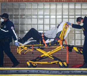 Paramedics wheel a patient wearing a breathing apparatus into the emergency room at Wyckoff Heights Medical Center, Monday, April 6, 2020, in New York. (AP Photo/John Minchillo)