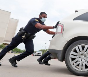 Amid concerns of the spread of COVID-19, Dallas ISD police officer Mylon Taylor helps push a car that ran out of gas while waiting in line for the weekly school meal pick up for students in Dallas, Thursday, April 9, 2020. (AP Photo/LM Otero)