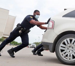 Amid concerns of the spread of COVID-19, Dallas ISD police officer Mylon Taylor helps push a car that ran out of gas while waiting in line for the weekly school meal pick up for students in Dallas, Thursday, April 9, 2020.