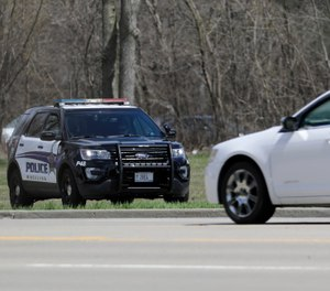 A Wheeling police officer checks the speed of the vehicles in Wheeling, Ill., Thursday, April 9, 2020.  (AP Photo/Nam Y. Huh)