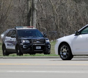 A Wheeling police officer checks the speed of the vehicles in Wheeling, Ill., Thursday, April 9, 2020.