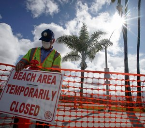 A city worker puts up signs to close part of the beach in Newport Beach, Calif., Friday, April 10, 2020. (AP Photo/Chris Carlson)