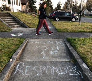 In this April 9, 2020 photo, pedestrians on an evening walk in Tacoma, Wash., stroll past a message written in sidewalk chalk thanking first responders serving the public during the coronavirus outbreak.