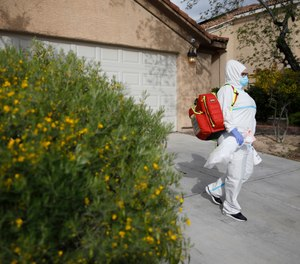 Paramedic Chelsea Monge of Ready Responders leaves a home after making a house call for a possible coronavirus patient Friday, April 10, 2020, in Henderson, Nev. Ready Responders recently began performing door-to-door COVID-19 tests in major U.S. cities including Reno, New Orleans, Las Vegas and New York City. (AP Photo/John Locher)
