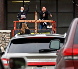 Paster Bruce Schafer, top right, preaches from a scissor lift during the first of two drive-in Easter services held by Grace Life Church in a parking lot in Monroeville, Pa., Sunday, April 12, 2020. (AP Photo/Gene J. Puskar)