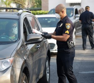 Surfside, Fla. Police Sgt. Jay Matelis, right, hands out a pair of cloth protective masks to a resident as she drives through, Monday, April 13, 2020, in Surfside.