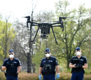 Police officers prepare a drone to find residents who fail to comply with the stay-at-home order implemented due to the coronavirus pandemic in Szolnok, Hungary, Monday, April 13, 2020.