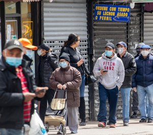 People wear face masks to protect against the coronavirus as they stand on line to grocery shop, Tuesday, April 14, 2020, in Corona neighborhood of the Queens borough of New York. (AP Photo/Mary Altaffer)