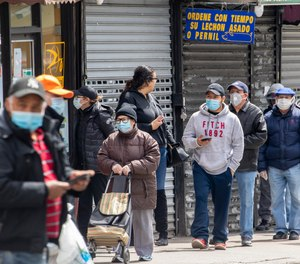 People wear face masks to protect against the coronavirus as they stand on line to grocery shop, Tuesday, April 14, 2020, in Corona neighborhood of the Queens borough of New York.