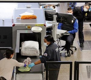 TSA agents wear masks as they screen passengers at Seattle-Tacoma International Airport Wednesday, April 15, 2020, in SeaTac, Wash. A whistleblower has filed a complaint claiming that the TSA has been hoarding 1.4 million N95 respirators despite instructing its employees to wear surgical masks.