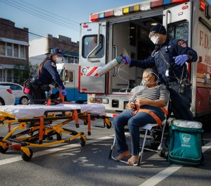 FDNY paramedics Elizabeth Bonilla, left, and Keith Kahara, right, prepare to load a patient on oxygen into their ambulance on an emergency call, Wednesday, April 15, 2020, in the Bronx borough of New York. (AP Photo/John Minchillo)