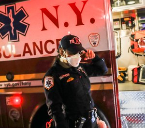 FDNY paramedic Elizabeth Bonilla center wipes a tear from her eye while wearing personal protective equipment due to COVID-19 concerns after an emergency call, Wednesday, April 15, 2020, in the Bronx borough of New York. (AP Photo/John Minchillo)